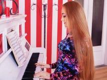A moça joga o piano O conceito do estilo de vida, música foto de stock