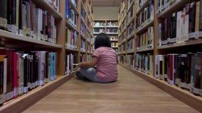 A moça lê um assento cômico no assoalho de uma biblioteca vídeos de arquivo