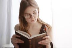 A moça lê um livro interessante Foto de Stock