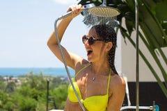 A moça lava sob um chuveiro em um maiô, no mar traseiro e nas folhas foto de stock royalty free