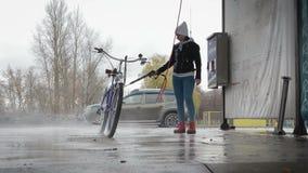 A moça lava sua bicicleta na lavagem de carros filme