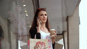 Moça lindo com valor dos pacotes perto da loja e fala no telefone filme
