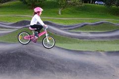 A moça livra a bicicleta no passeio na montanha do obstáculo Imagem de Stock Royalty Free