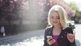 Moça loura bonita em um vestuário desportivo que anda abaixo da aleia de sakura, sonhadoramente sorrindo, usando seu telefone Apr video estoque
