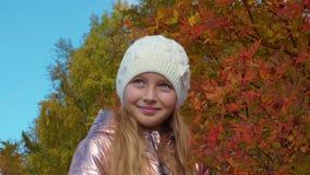 Moça loura bonito no chapéu branco que está no parque do outono filme