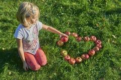 Moça loura da criança com a forma vermelha do coração das maçãs que encontra-se na grama Imagens de Stock