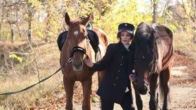 A moça luxuoso anda com os dois cavalos na floresta no tempo morno do outono filme
