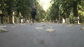 Moça magro que escuta a música e o corredor no parque em um dia ensolarado bonito do outono - video estoque