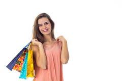 A moça mantém em seu ombro muitos pacotes bonitos e fundo branco isolado de sorriso Foto de Stock Royalty Free