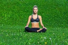A moça medita na posição da ioga Fotografia de Stock