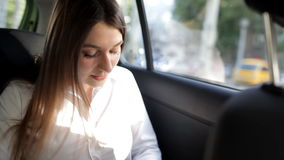 A moça monta em um táxi e está preparando-se para uma reunião de negócios, fazendo anotações no bloco de notas filme