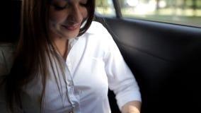 A moça monta em um táxi e está preparando-se para uma reunião de negócios, fazendo anotações no bloco de notas video estoque