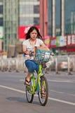 A moça monta uma bicicleta pública da parte, baixa do Pequim, China Fotos de Stock