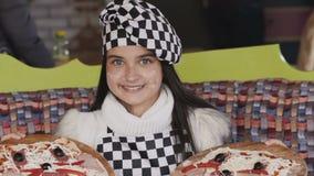 A moça mostra duas pizzas na câmera lentamente video estoque