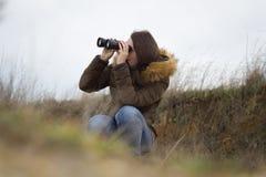 Moça/mulher bonitas que olha para fora pelo telescópio t do ornitology Imagens de Stock Royalty Free