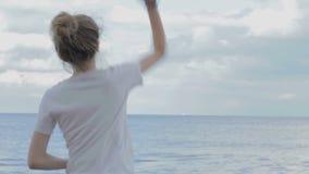 A moça na camisa branca de T com cabelo amarrou joga acima pedras no mar com o céu dramático da noite Imagem de Stock