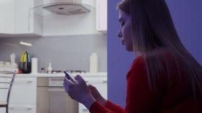 A moça na camiseta é mensagem com os amigos na cozinha vídeos de arquivo