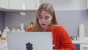 A moça na camiseta vermelha usa o portátil na cozinha vídeos de arquivo