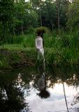 A moça na grinalda mergulha na água no festival popular Foto de Stock Royalty Free