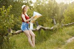 Moça na natureza com chapéu e mapa verão Fotografia de Stock