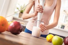 Moça na posição saudável do estilo de vida da cozinha que faz o puré com close-up do misturador da mão foto de stock