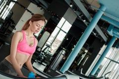 Moça na posição saudável do estilo de vida do gym na escada rolante cansada imagem de stock royalty free