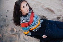 Moça na praia que encontra-se na areia Ela que veste nas calças de brim e na camiseta colorida Mulher com cabelo longo em uma lin Fotos de Stock Royalty Free