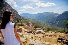 Moça na roupa branca que está na rocha em Grécia imagens de stock royalty free