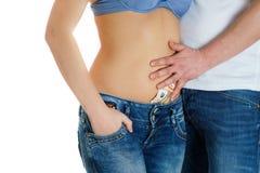 A moça nas calças de brim e um estômago despido equipam o toque dela que paga o dinheiro Imagem de Stock