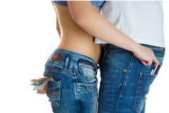 Moça nas calças de brim e um estômago despido que roubam o cartão de crédito do homem Foto de Stock Royalty Free
