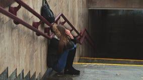 A moça nas escadas no assento comprimido metro apenas obscurece a cara com seu grito do handsand outono video estoque