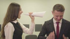 Moça nervosa no papel dobrado vestuário formal sob a forma de um chifre e gritar no colega masculino no escritório moderno video estoque