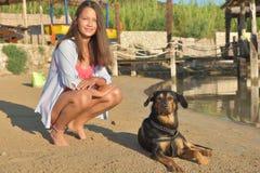 Moça no biquini e no cão na praia imagem de stock royalty free