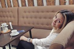 A moça no café no sofá olha do ombro de trás, girando sua cabeça para trás Fotos de Stock
