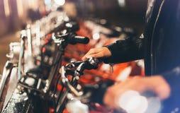 Moça no casaco de cabedal preto usando a bicicleta na luz do bokeh do fulgor da iluminação do fundo na cidade atmosférica da noit fotos de stock royalty free