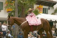 A moça no cavalo cor-de-rosa dos passeios do vestido na festa espanhola velha anual dos dias guardou cada agosto em Santa Barbara fotografia de stock royalty free