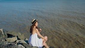 Moça no chapéu de palha que senta-se na praia de pedra fecha seus olhos, aprecia o sol filme