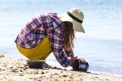 A moça no chapéu do sol que senta-se em seus quadris e jogador das lavagens escala comer Cozinhando o potenciômetro Imagem de Stock Royalty Free