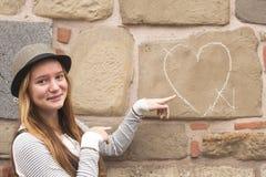 Moça no chapéu perto da parede com coração tirado do giz Foto de Stock Royalty Free
