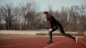 A moça no estádio executa o músculo que estica exercícios vídeos de arquivo