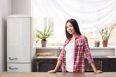 A moça no estilo de vida saudável da cozinha que inclina-se na tabela que olha a câmera relaxou imagens de stock