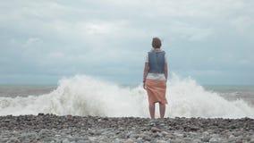 Moça no olhar da praia em ondas altas do oceano - Geórgia video estoque