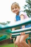 Moça no quadro de escalada no campo de jogos Fotos de Stock