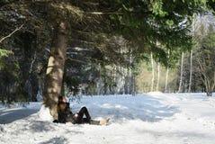 Moça no revestimento preto que senta no remendo thawed uma árvore na neve em uma floresta selvagem fabulosa Imagem de Stock