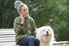 Moça no revestimento verde e em dreadlocks coloridos que fala sobre imagem de stock royalty free