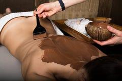 Moça no salão de beleza dos termas, tratamento do envoltório do corpo do chocolate, rejuvenescimento da pele Conceito do tratamen fotos de stock royalty free