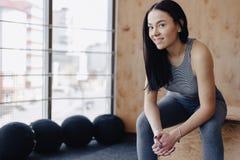 Moça no sportswear em um gym em um fundo simples, em um tema da aptidão, em um crossfit e no esporte imagens de stock royalty free