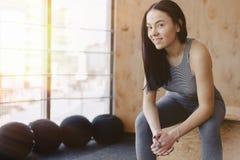 Moça no sportswear em um gym em um fundo simples, em um tema da aptidão, e no esporte fotos de stock