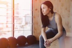 Moça no sportswear em um gym em um fundo simples, em um tema da aptidão, e no esporte imagens de stock