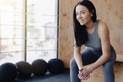 Moça no sportswear em um gym em um fundo simples, em um tema da aptidão, e no esporte foto de stock royalty free